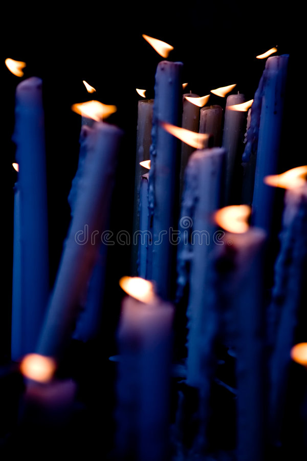 Candles in the altar. Candles blue tint applied, burning in the altar of the church royalty free stock images