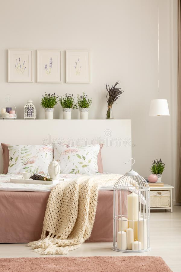 Candles in bird cage placed on the floor by double bed with breakfast tray and knit blanket standing in real photo of white stock image