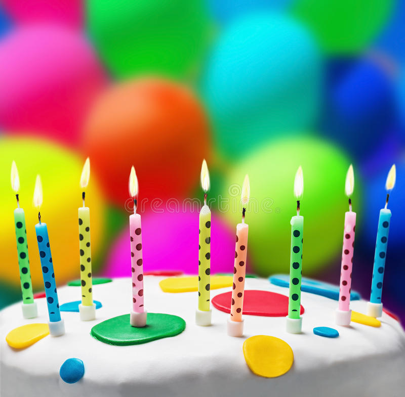 Candles on a birthday cake on the background of balloons. Burning candles on a birthday cake on the background of balloons stock photos