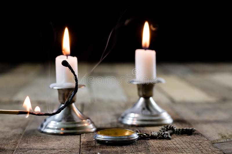 Candles burning in candlesticks on a wooden table. Silver candle stock image