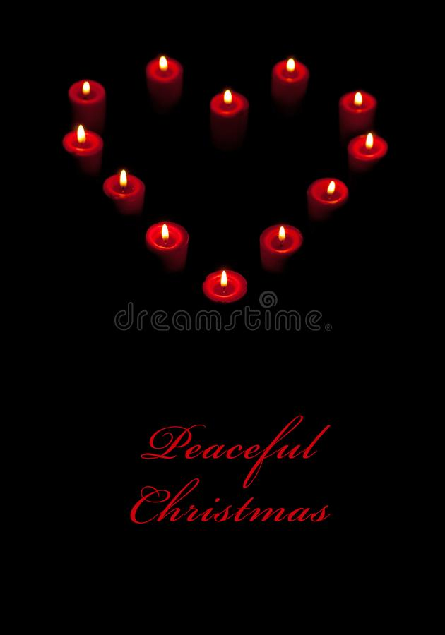 Candles burning in a shape of heart against dark background with text Peaceful Christmas; stock images