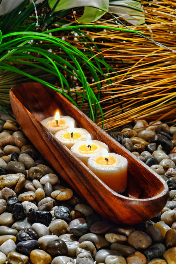 Candles Burning in Wood Vessel in a Holistic Spa. Votive candles burning with a soft glow flame in a traditional carved wood vessel holder on a bed of pebbles stock photos