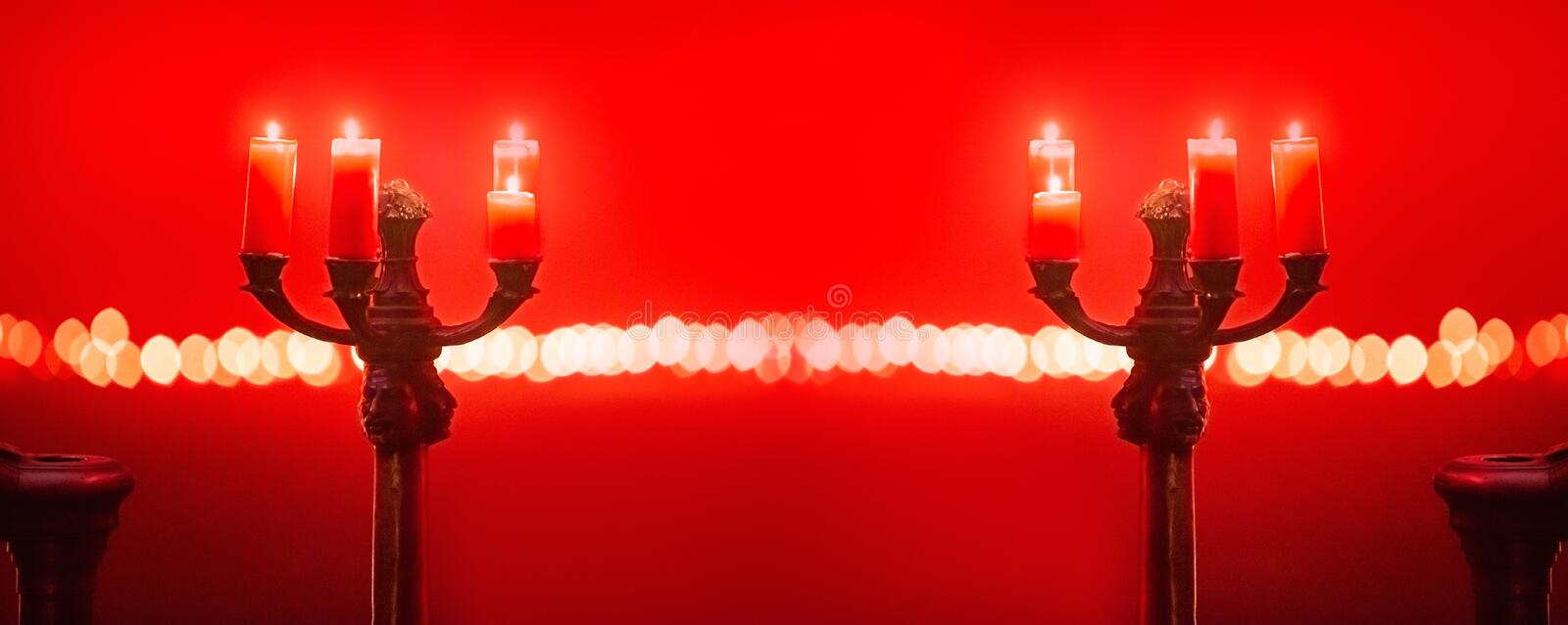 Candles in candlestick holder in red room royalty free stock photography