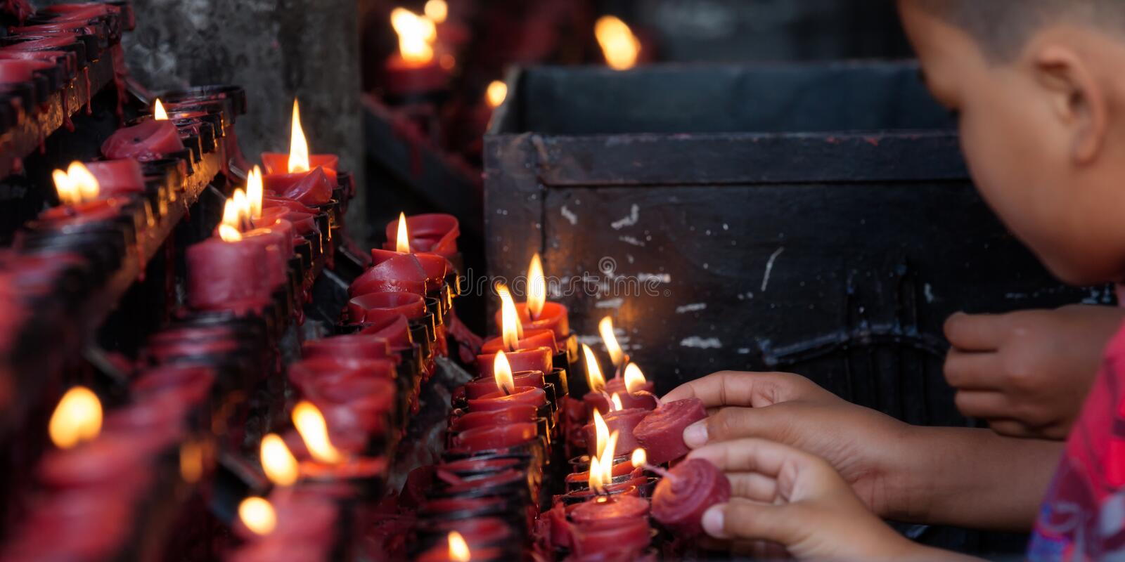 Candles. Children light candles in a church stock image