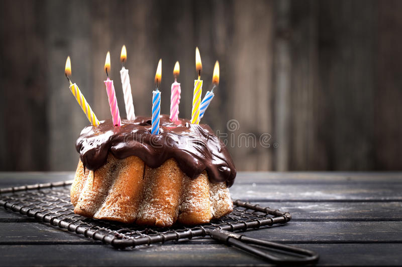 Candles on chocolate cake stock images