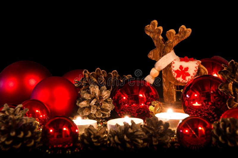 Candles with christmas wooden deer in atmospheric light royalty free stock image