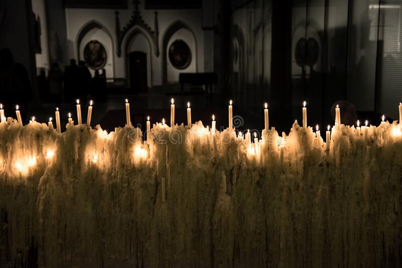 Candles in church in the dark. Thin candles burning on melting wax in Orthodox church in the dark stock image