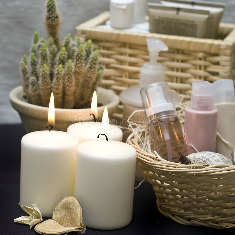 Candles and cosmetics. Thre white candles and baskets with cosmetics, bathroom decoration royalty free stock images