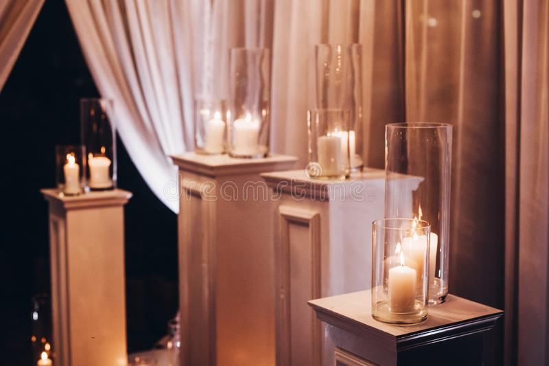 Candles in glass lanterns and arch, stylish wedding decor for evening wedding ceremony in garden, light close up. beautiful roman. Tic place for love celebration royalty free stock images
