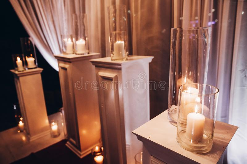 candles in glass lanterns and arch, stylish wedding decor for evening wedding ceremony in garden, light close up. beautiful roman royalty free stock image