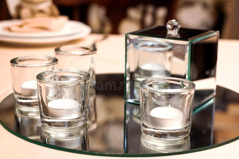 Candles in glasses standing on a table stock photo