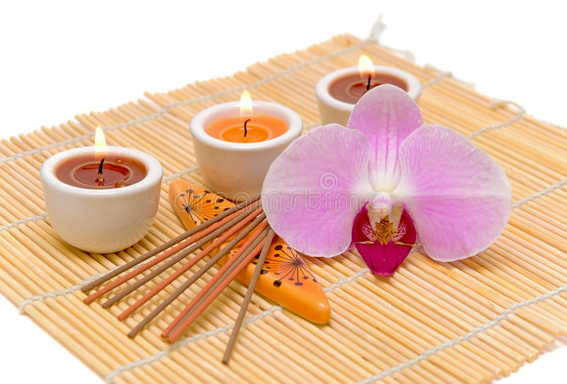 Candles, incense sticks and orchid on a white back royalty free stock images