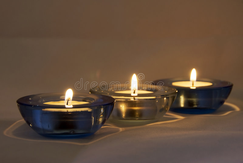 Candles lighted - atmosphere. Three candles lighted in a row - romantic atmosphere stock photography
