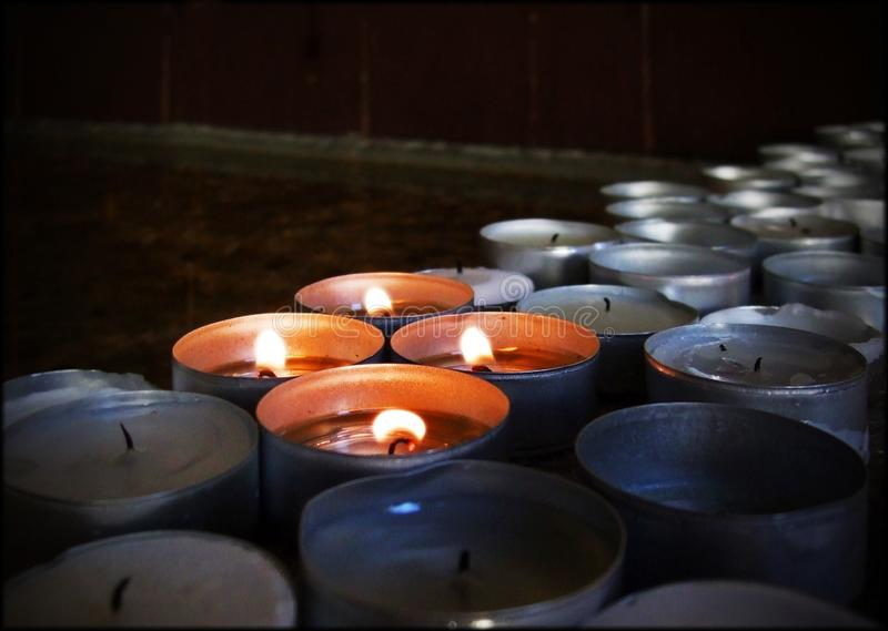 A group of many candles with four of them burning royalty free stock photos