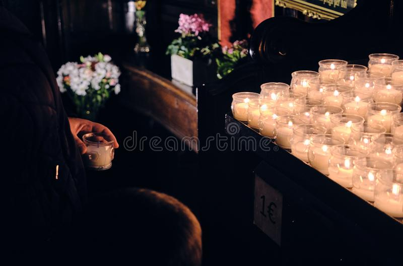 Candles lighting church and children offering coin.  royalty free stock image