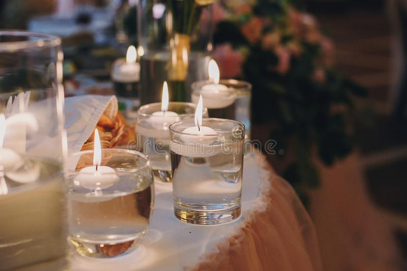 Candles with lights in glasses with water, stylish wedding decor for evening ceremony or at reception in restaurant. Spiritual royalty free stock photos