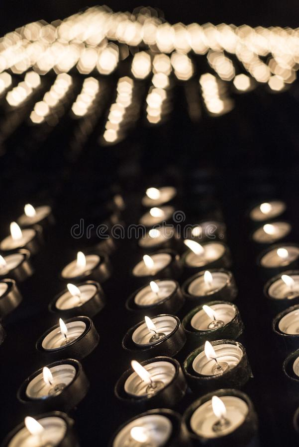 Candles lit in a Christian shrine for spiritual offerings. In southern Spain royalty free stock image
