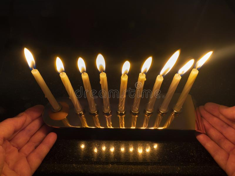 A candlestick with fully lit candles on the last day of the holiday of Hanukkah in female hands. royalty free stock images