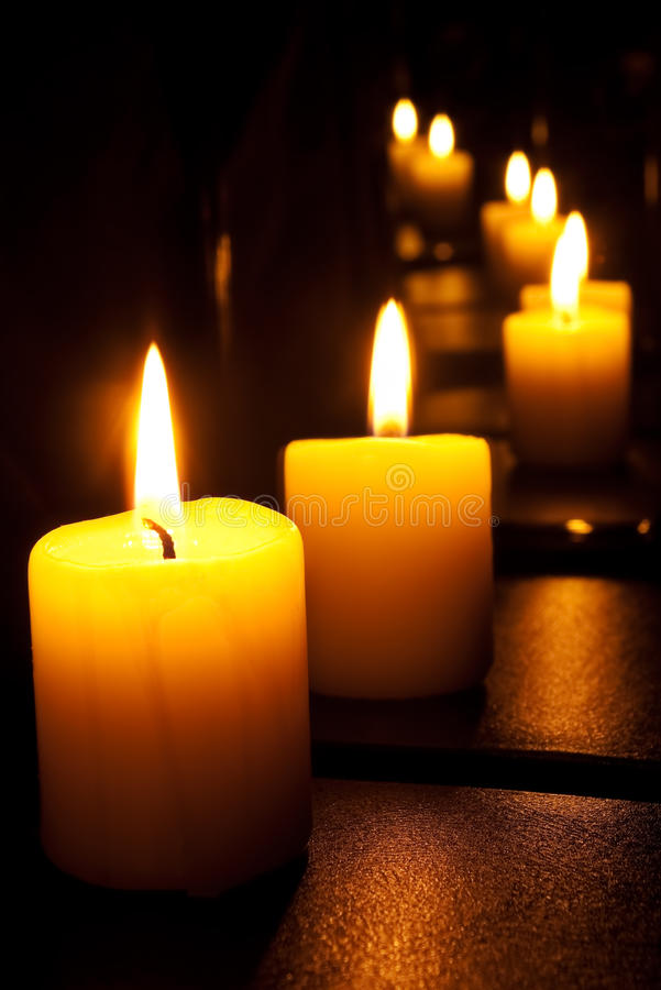 Candles in a mirror. Candle, set of times reflected in mirrors royalty free stock photos