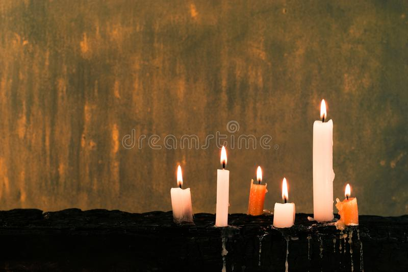 Candles on an old wooden burnt table. Beautiful dark background. Religious concept. royalty free stock photography