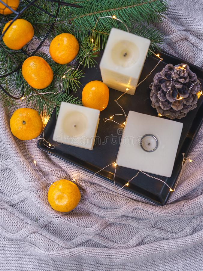 Candles, orange tangerines, pine cone on black tray and cosy fairy lights on knitte plaid backgroundand. Christmas decorations stock images