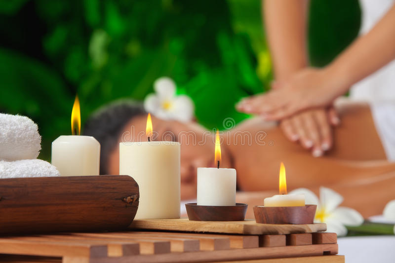 Candles. Portrait of young beautiful woman in spa environment. focused on candles stock photography