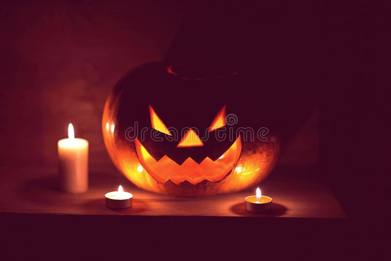 Candles and pumpkin for Halloween in a cramped room stock photos