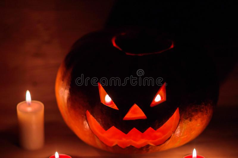 Candles and pumpkin for Halloween in a cramped room royalty free stock photography
