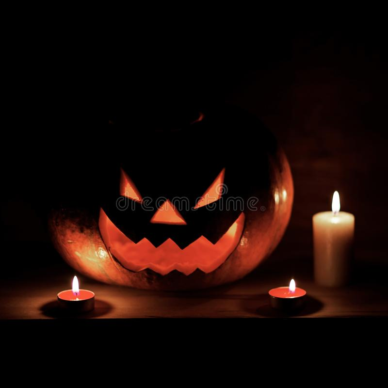 Candles and pumpkin for Halloween in a cramped room royalty free stock photo