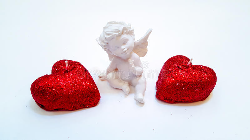 candles in the shape of hearts covered with red sequins and Cupid on a white background stock images