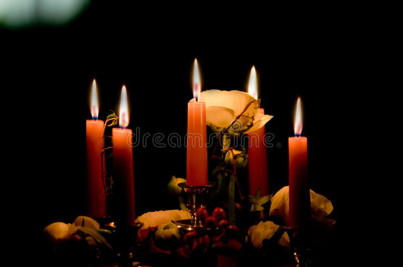 Candles shine in the dark and illuminate the roses given by your royalty free stock photos