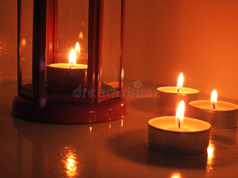 Candles in transparent chandeliers. Candles in red and yellow transparent chandeliers stock photos