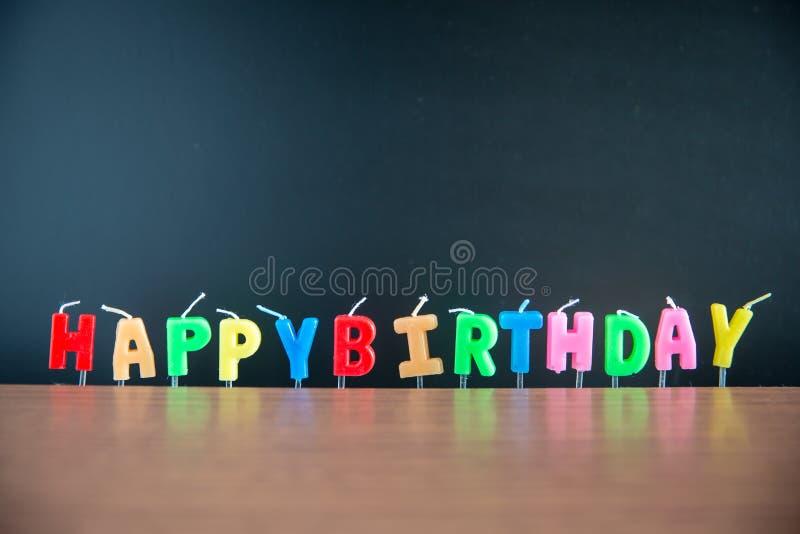 Candlestick alphabet word happy birthday with blackboard on wooden floor. stock photos