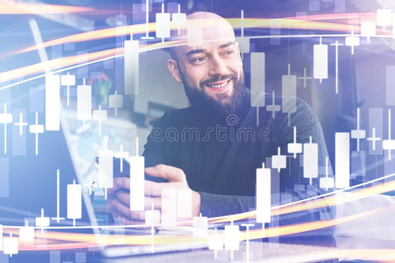 Candlestick chart in foreground. In background man in black turtleneck working on laptop. Businessman waiting for meeting stock photos