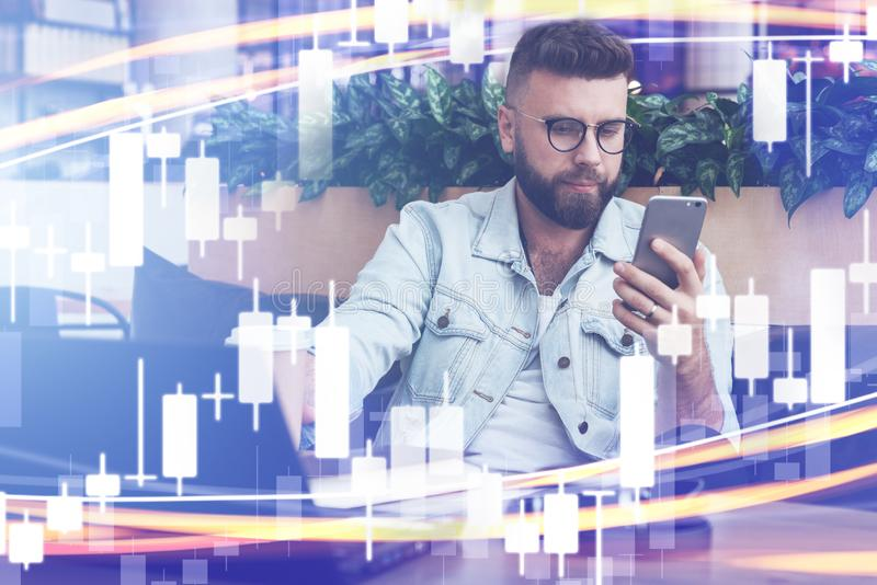 Candlestick chart in foreground. In background man in trendy glasses sits works on laptop, uses smartphone. Online marketing. Candlestick chart in foreground. In royalty free stock photos