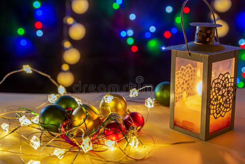Candlestick with glowing candle, glowing lights and different colors balls are on the shiny table/background. There are different colors lights on the stock photo