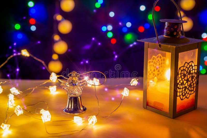Candlestick with glowing candle, glowing lights and gold angel in tne centre are on the shiny table/background. There are different colors lights on the stock photography