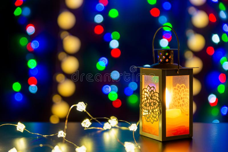 Candlestick with glowing candle and glowing lights are on the shiny table/background. There are different colors lights. Candlestick with glowing candle and royalty free stock photography