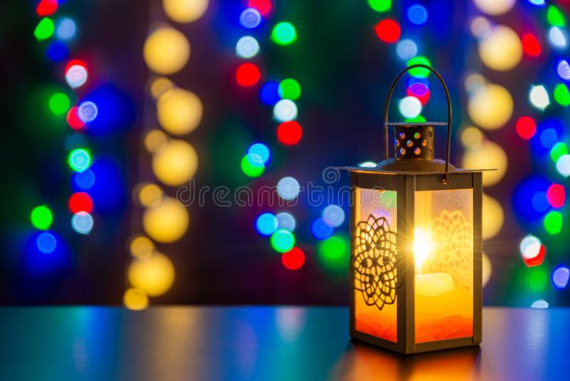 Candlestick with glowing candle is on the shiny table/background. Different colors lights are on the background. Candlestick with glowing candle is on the shiny stock photography