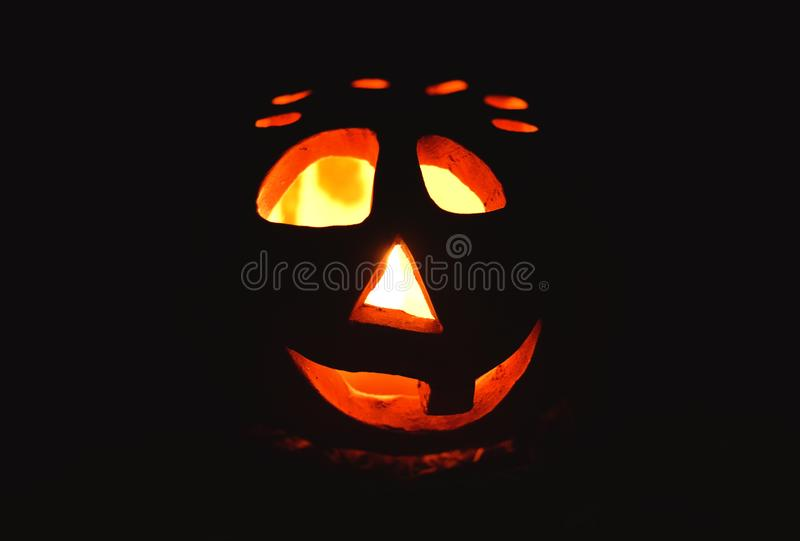 Candlestick pumpkin with a burning candle inside on dark background, symbol of Halloween stock photos