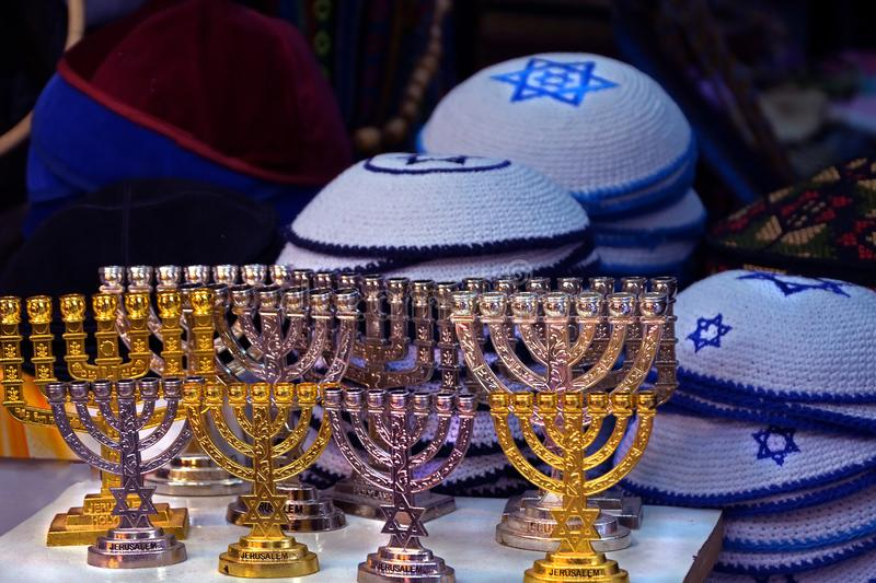 Candlesticks of the menorah are gold and silver. Knitted multi colored kipa are sold in the market in Jerusalem royalty free stock photography