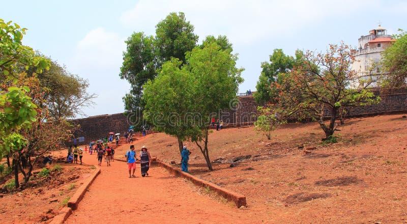 CANDOLIM, GOA, ÍNDIA - 11 DE ABRIL DE 2015: Caminhada não identificada dos turistas perto do forte Aguada, Goa fotografia de stock royalty free