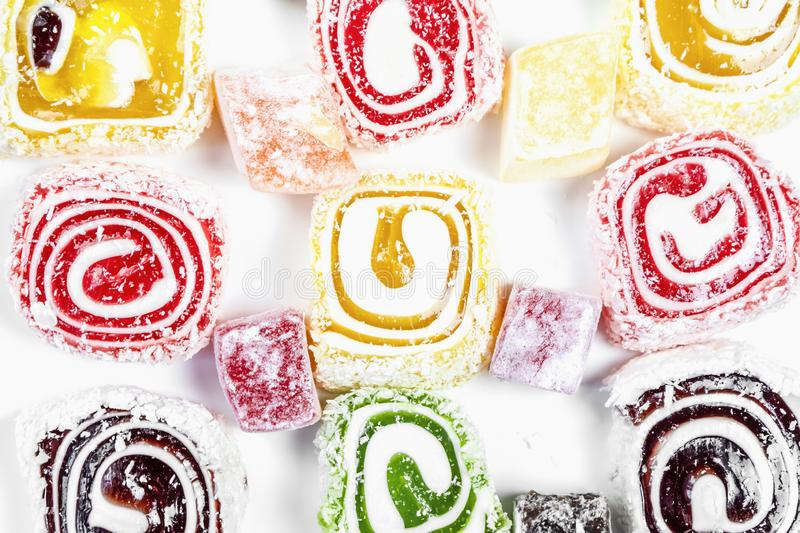 Candy background. Colored candy wrapped in a roll and sprinkled with coconut flake. Turkish delight royalty free stock images