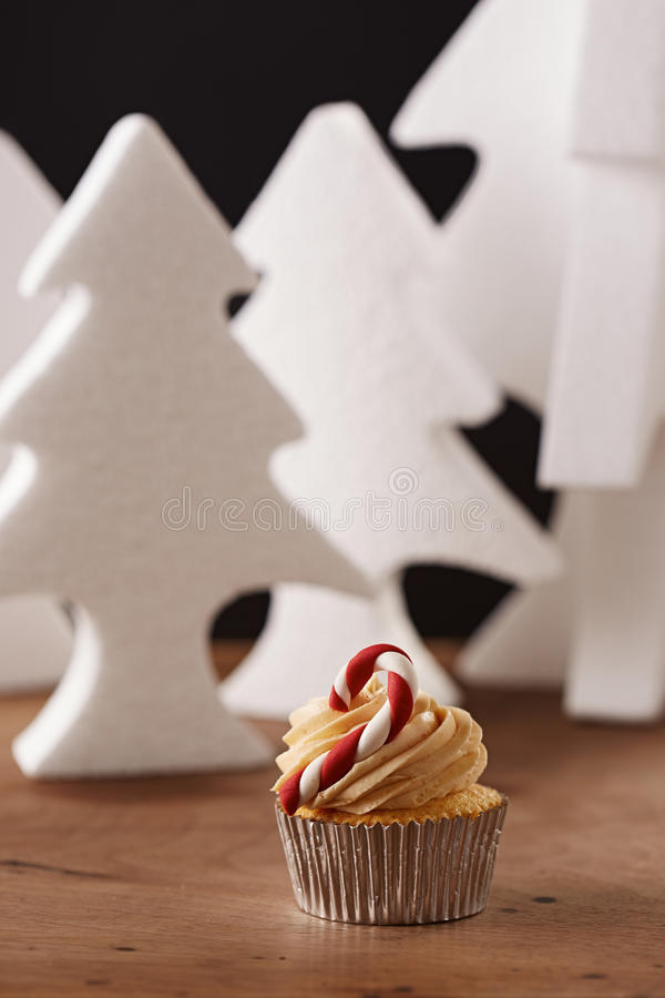 Candy bar cupcake on Christmas background. Candy bar cupcake on white Christmas trees background stock photo