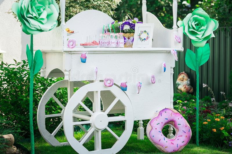Candy bar. Decor for baby`s or child`s Birthday party. wooden canopy with wheels for children`s holiday stock image