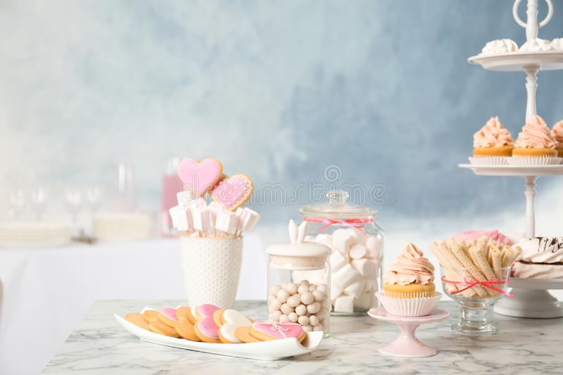 Candy bar with different sweets on white marble table royalty free stock image
