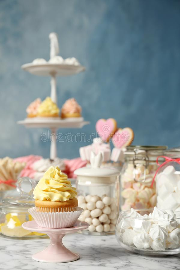 Candy bar with different sweets on white marble table against color background stock photos