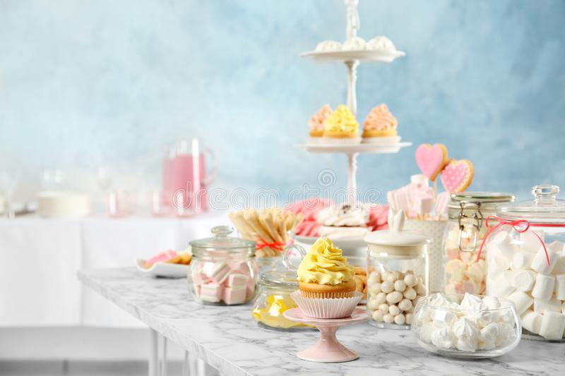 Candy bar with different sweets on white marble table. Space for text stock photo