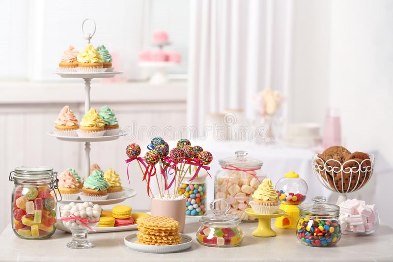 Candy bar with different sweets on white table against blurred royalty free stock images