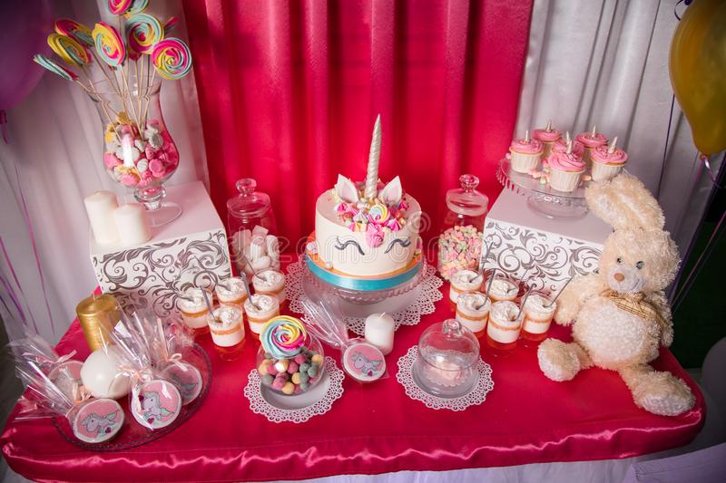 Candy bar for the first birthday for little baby girl. Sweet table and big unicorn cake stock image